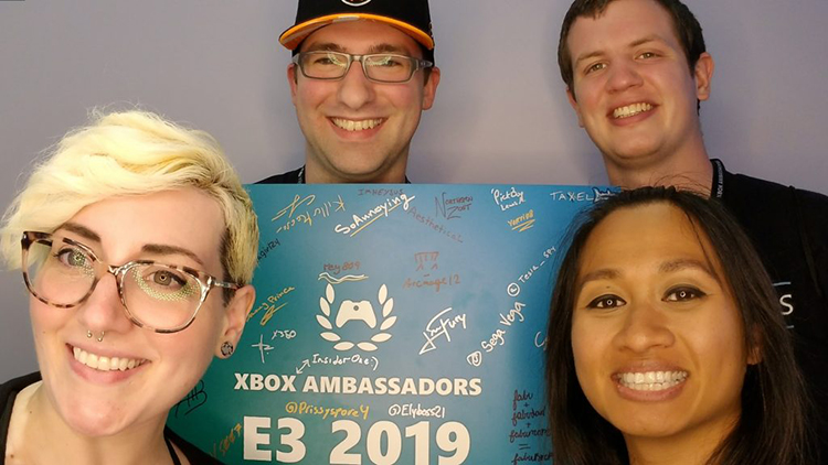 four-community-managers-smiling-with-e-3-autograph-board
