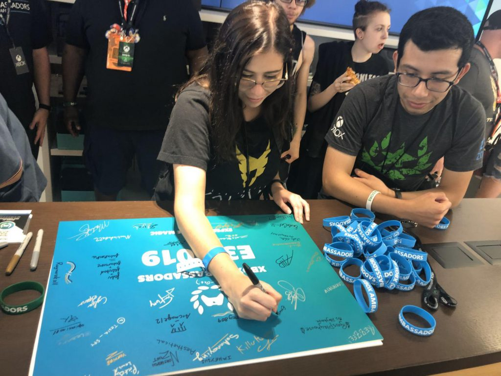 Emericagirl signing a poster board with the Ambassadors logo on it