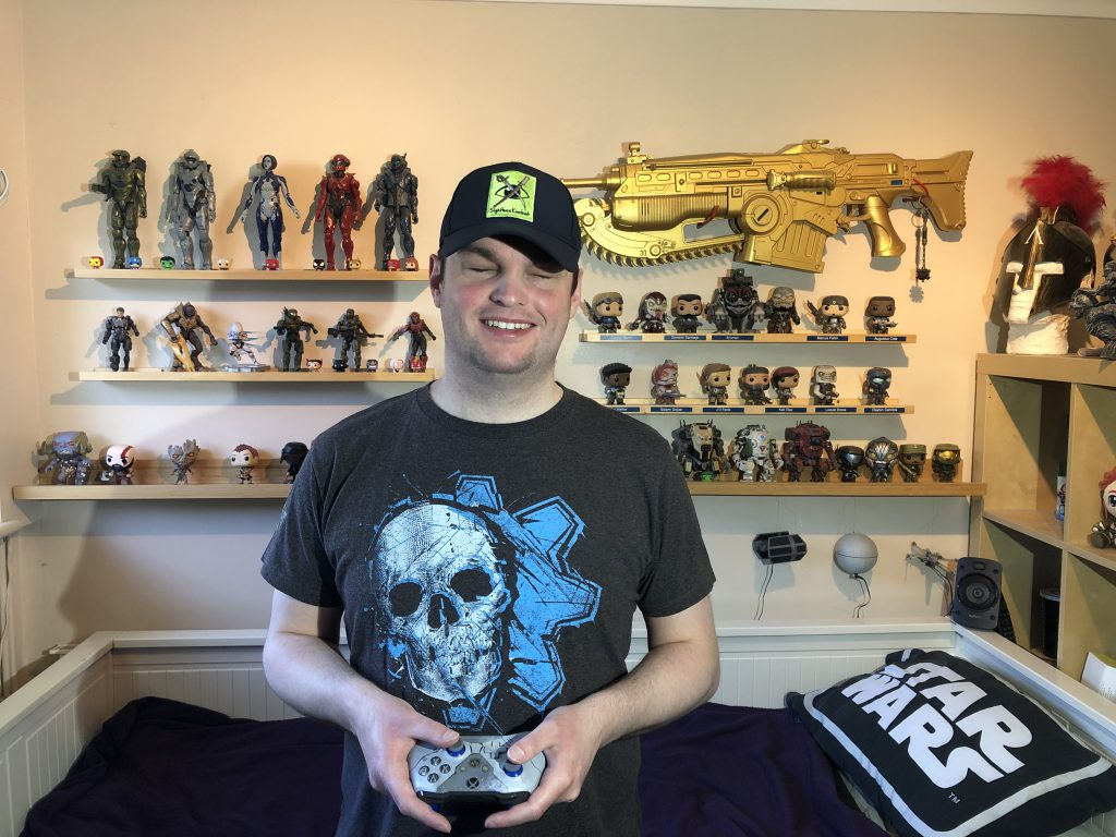 Sightless stands holding a Gears 5 Kait Diaz controller, wearing jeans and a Gears 5 shirt emblazoned with the Ice Omen. Behind him is just a part of his gaming collection, with 16 Gears Pop Vinyls, featuring General Raam and a Brumak amongst others, along with Halo Pops and other larger scale figures. Behind and to his left, above the majority of the figures is a gold Gears Of War 4 lancer, in pride of place.