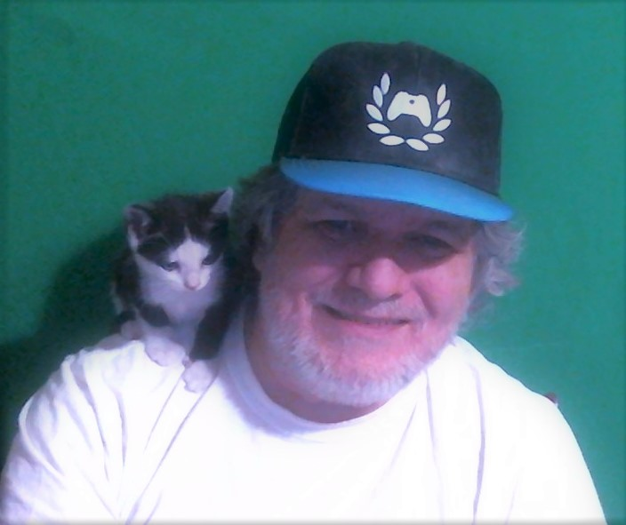 CerebralPaul#921, wearing a white shirt and a black and blue Xbox Amabssadors hat, smiles front of a green screen. His black and white cat perches on his shoulder.