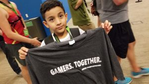 "Boy holding a tshirt that says ""Gamers. Together."""