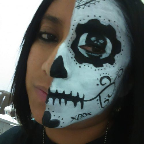 Dark-haired lady with face paint on half her face to look like a skull