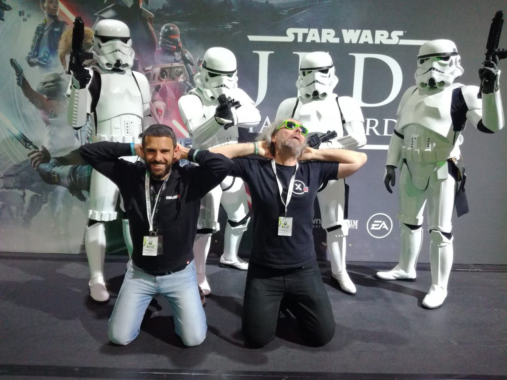ThorX360 and a friend posing as a prisoner of a group of Stormtroopers in front of a sign for the Star Wars Jedi Fallen Order
